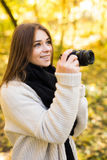 Girl take photo with camera in yellow autumn Royalty Free Stock Images