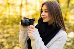 Girl take photo with camera in yellow autumn Royalty Free Stock Photo