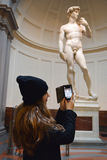 Girl take photos David by Michelangelo in Galleria dell Accademia, Florence royalty free stock photo