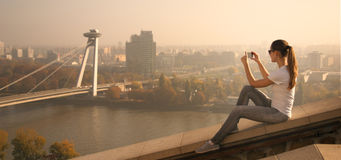 Girl take picture Bratislava. Girl sitting over the city over the river and take pictures Royalty Free Stock Photo