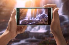 Girl take a picture of man on a waterfall stock photography