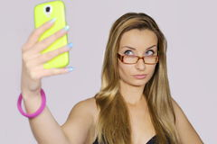 Girl take a self portrait with her smart phone Royalty Free Stock Photos