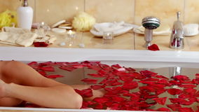 The girl takes a bath with rose petals. The camera stock footage