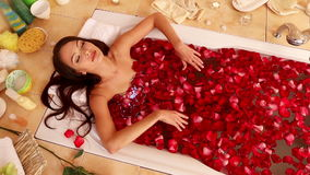The girl takes a bath with rose petals. The camera stock video footage