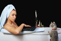 Girl takes a bath and is working with laptop royalty free stock photography