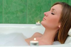 The girl takes a bathtub at candles Stock Image