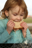 Girl takes big bite of sandwich. A girl sits at a table outdoors eating a sandwich Royalty Free Stock Photo