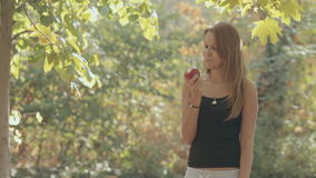 Girl takes a bite red of apple in the park. And smiles stock video