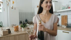 Champagne at christmas. The girl takes champagne and glasses and carries them to the festive table stock video footage