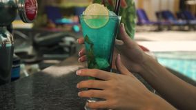 Girl takes a cocktail from the bar. Hands of a girl raise a green cocktail from the bar by the pool stock footage