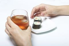 The girl takes a glass of whiskey from the table with ice. Another hand takes from the plate of sushi. Rest of the day off. Stock Photos
