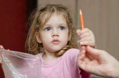 Girl takes from the hands of moms pencil Royalty Free Stock Photography