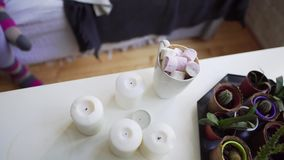 Girl takes a hot drink with marshmallows from a white table, flat lay. 4k stock video footage