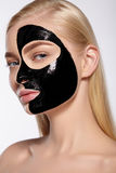 Girl takes off black cosmetic mask from her face. The girl takes off a black cosmetic mask from her face Stock Photo