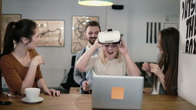 Girl takes off her glasses virtual reality after using the new app share experiences with team in the startup office. Stock Photo
