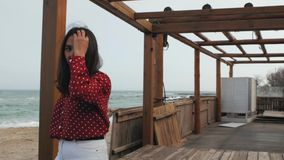 Girl takes off sunglasses against a wooden structure.  stock footage