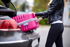 The girl takes out her pink suitcase from the trunk. The girl is beautiful, with glasses, the blonde pulls her pink suitcase out of the trunk of the car Stock Photography