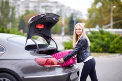 The girl takes out her pink suitcase from the trunk. The girl is beautiful, with glasses, the blonde pulls her pink suitcase out of the trunk of the car Stock Photo