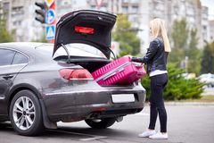 The girl takes out her pink suitcase from the trunk. The girl is beautiful, with glasses, the blonde pulls her pink suitcase out of the trunk of the car Royalty Free Stock Images
