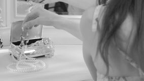 Girl takes a pearl necklace. He is sitting near a mirror. chic luxury interior stock footage