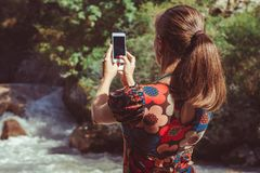 Girl takes on the phone nature. Girl shoots a mountain river on her phone stock photo