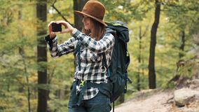 Girl Takes Photo. Happy, female backpacker taking photo with smartphone on amazing hiking trip, standing cheerfully in lovely, fall forest stock footage