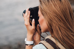 Girl takes photographs with vintage photo camera Royalty Free Stock Image