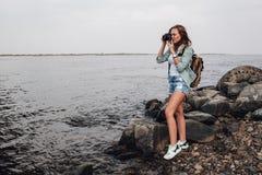 Girl takes photographs with vintage photo camera Stock Photos