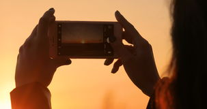 Girl takes a picture of a beautiful sunset on a mobile phone