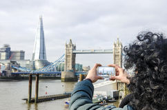 Girl takes picture of The Shard and Tower Bridge. Girl takes picture with smartphone of the Shard and Tower Bridge on Thames river in London, UK Stock Photos
