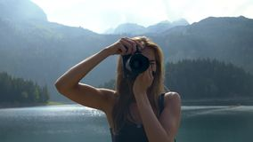 Girl takes a picture stands against the background of the landscape. Girl is shooting with a camera on the background of a black lake, moving the device from stock video