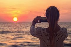 A girl takes a picture of the sunset. A girl at the ocean takes a picture of the sunset royalty free stock image