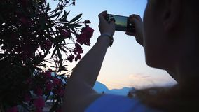 A girl takes pictures of flowers on a smartphone at sunset with mountains in the background. A girl takes pictures of flowers on a smartphone at sunset with stock video footage