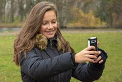 Girl takes pictures with her mobile phone. In park Stock Photography