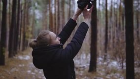 The girl takes pictures of herself in the forest on the camera. Selfi on the nature. cinematic shot, slow motion.  stock video footage