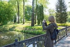 Girl takes pictures landscape and doing selfie on cell phone. Royalty Free Stock Image