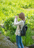 Girl takes pictures landscape and doing selfie on cell phone. Royalty Free Stock Images