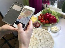 A girl takes pictures of a pizza on a smartphone. Necessary ingredients are on the table: cheese, sausage, pizza base and vegetabl. Es Royalty Free Stock Photos