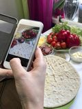 A girl takes pictures of a pizza on a smartphone. Necessary ingredients are on the table: cheese, sausage, pizza base and vegetabl. Es Royalty Free Stock Photography