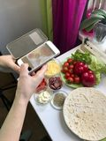 A girl takes pictures of a pizza on a smartphone. Necessary ingredients are on the table: cheese, sausage, pizza base and vegetabl. Es Royalty Free Stock Photo