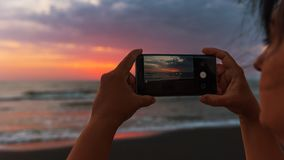 Girl takes pictures on smartphone, dawn on sea royalty free stock photo