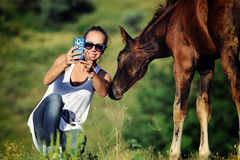 Girl takes selfie with foal Royalty Free Stock Photo