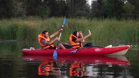 Girl makes selfie in a kayak, the guy shows thumbs up. Slow motion stock video