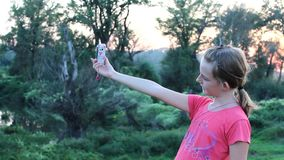 Girl takes selfies of herself with smart phone stock video