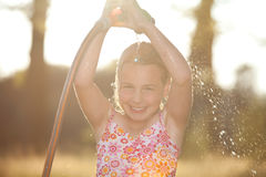 Girl takes a shower in the garden, summer Stock Photo