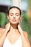 Girl takes a shower near the pool. Girl enjoying a shower. Beautiful brunette woman in a white swimsuit near the pool. royalty free stock image