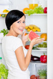 Girl takes watermelon from opened fridge Stock Photos