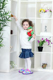 Girl taking all toys from the shelves Royalty Free Stock Photography