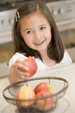 Girl taking apple from fruit basket at home Royalty Free Stock Image