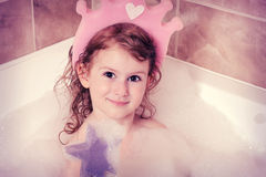 Girl is taking a bath. Small pretty girl is taking a bath and  with a foam Royalty Free Stock Image